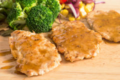 Pork cube steak topped with pepper sauce. And creamy salad on wood plate royalty free stock image