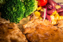 Pork cube steak topped with pepper sauce. And creamy salad on wood plate stock image