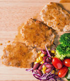 Pork cube steak topped with pepper sauce. And creamy salad on wood plate royalty free stock images