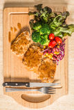 Pork cube steak topped with pepper sauce. And creamy salad on wood plate royalty free stock photography