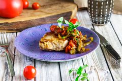 Pork cutlet with vegetable sauce on a violet plate stock photo