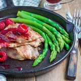 Pork cutlets with raspberry sauce and asparagus in iron cast pan, square. Format royalty free stock photography