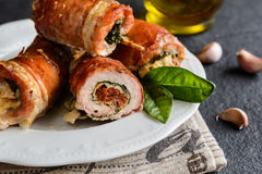 Pork cutlets wrapped in bacon and stuffed with cheese, spinach and sun dried tomato Stock Image