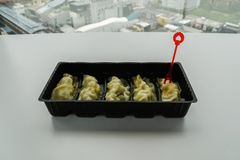 Pork dumpling in black container with red fork Royalty Free Stock Image