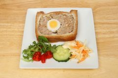 Gala pie and salad. Pork and egg gala pie with salad garnish on a plate on a wooden tabletop Royalty Free Stock Images