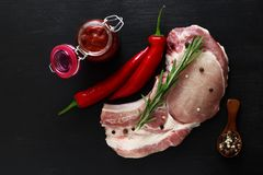 Pork entrecote raw meat with rosemary, pepper and red sauce.  Royalty Free Stock Photos