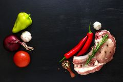 Pork entrecote raw meat with rosemary, and vegetables onion, pepper, garlic and tomato.  Stock Images
