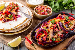 Pork fajitas with onions and colored pepper, served with tortillas. Salsa and sour cream, selective focus Royalty Free Stock Photo