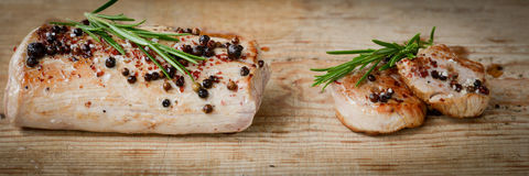 Pork fillet on a rustic board. Pork meat rosted on a rustic table Stock Photo