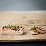 Pork fillet on a rustic board. Pork meat rosted on a rustic table Royalty Free Stock Image