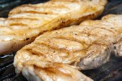 Pork Fillet Steaks in Griddle Pan. Pork fillet steaks close up frying in a griddle pan Stock Images