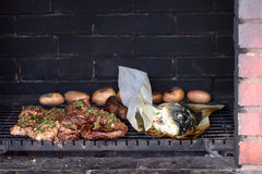 Pork and fish on grill at fireplace. Bricks royalty free stock photography