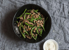 Pork and green beans stir fry on a dark table. Top view royalty free stock photography
