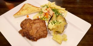 Pork grill steak menu set has baked potato with butter with vegetable salad. Pork grill steak set has baked potato with butter, vegetable salad, french fried and stock photo