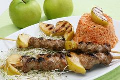 Pork grilled with apples. Pork sticks barbecue with rice salad germs and apples Royalty Free Stock Photos