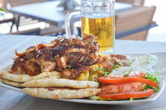 Pork gyros on a plate with salad and a bear. Pork gyros on a plate with salad and a glass of bear Royalty Free Stock Images