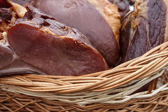 Pork ham placed in a wicker basket Royalty Free Stock Image