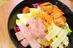 Pork and ham salad. On the black dish Stock Photo
