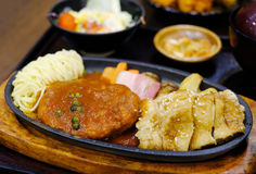 Pork hamburg on hot plate. Pork hamburg, bacon and fried chicken ontop with teriyaki sauce stock photos