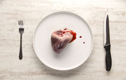 Pork heart on a white plate. Raw pork heart on a white plate served with blood Stock Photo