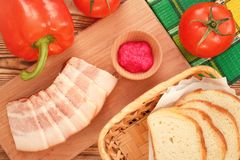Pork jowl bacon with fresh vegetables. Pork jowl bacon sliced on wooden plate with fresh vegetables stock photography