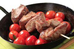 Pork kebab and tomatoes Stock Photos