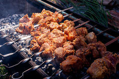 Pork kebabs grilling outside. At nature, sunny summer day Royalty Free Stock Photo