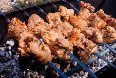 Pork kebabs grilling outside. Sunny summer day Royalty Free Stock Image