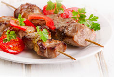 Pork kebabs served with vegetables on a white plate Royalty Free Stock Images