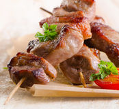 Pork kebabs served with vegetables on wooden table Royalty Free Stock Photography