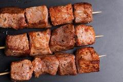 Pork kebabs on wooden skewers. On a dark baking Royalty Free Stock Photos