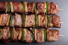 Pork kebabs on wooden skewers. On a dark baking Stock Photography