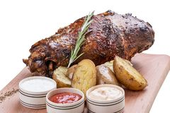 Pork knuckle with baked potatoes and sauces royalty free stock photos