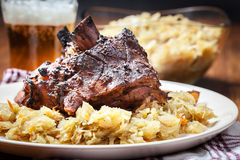 Pork knuckle with fried sauerkraut and baked potatoes Royalty Free Stock Images