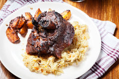 Pork knuckle with fried sauerkraut and baked potatoes Stock Images