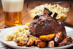 Pork knuckle with fried sauerkraut and baked potatoes Royalty Free Stock Photography