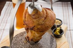 Pork knuckle roast served with cabbage and pickled vegetables, traditional sunday lunch dinner meal. Pork knuckle roast served with cabbage and pickled stock image