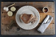 Pork leg ham on the plate. On a rough rustic wooden background - top view - flat lay Royalty Free Stock Image