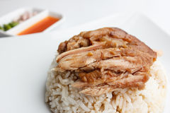 Pork leg with rice close up on white background. Pork leg with rice close up and sauce on white background stock photo