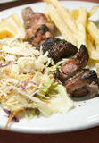 Pork liver kabob meal from Tunis Tunisia. Pork and liver shish kabab meal with salad and French fried potatoes stock photography
