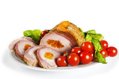 Pork loin. Delicious pork loin with apricot and baby tomatos on the plate Royalty Free Stock Image