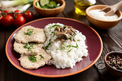 Pork loin fillets with rice and mushrooms. On a wooden background royalty free stock photography