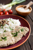 Pork loin fillets with rice and mushrooms. On a wooden background stock images