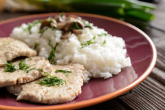 Pork loin fillets with rice and mushrooms. On a wooden background royalty free stock images