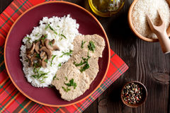 Pork loin fillets with rice and mushrooms. On a wooden background stock photo