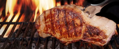 Pork Loin Steak On Hot Flaming Barbecue Grill With Fork. Browned Pork Loin Steak On The Hot Barbecue Charcoal Grill With Fork, Bright Flames Of Fire On The Black Royalty Free Stock Photography