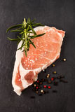 Pork loin steak with rosemary, peppercorn and coarse salt Royalty Free Stock Photography