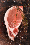 Pork loin steak with thyme, peppercorn and coarse salt on an roa Royalty Free Stock Photography