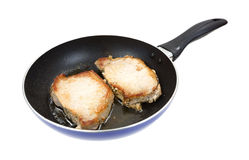 Pork loin steaks frying in pan Stock Image