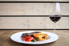 Pork meal with potato slices and a tomato. In a big white plate on a wooden surface with a glass of wine stock images